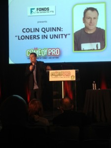 Colin Quinn on stage deliverying is keynote speech.